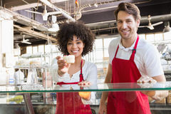 Smiling waitress in red apron offering cupcake Royalty Free Stock Image