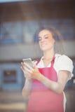 Smiling waitress sending a text Royalty Free Stock Photo