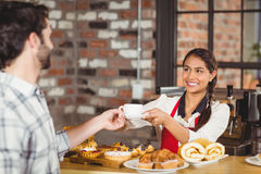 Smiling waitress serving a client Stock Photography