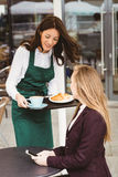 Smiling waitress serving a coffee and croissant Stock Photography