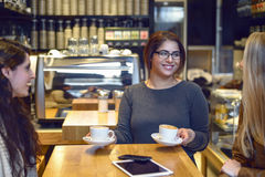 Smiling waitress serving coffee Royalty Free Stock Photography