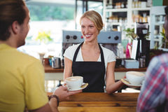 Smiling waitress serving cup of coffee to customer Stock Photo