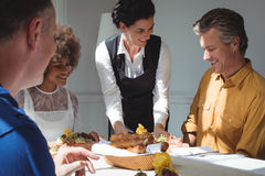 Smiling waitress serving food to customers. In restaurant Stock Photography
