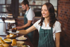 Smiling waitress serving a muffin Royalty Free Stock Images