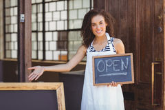 Smiling waitress showing chalkboard with open sign Stock Photos