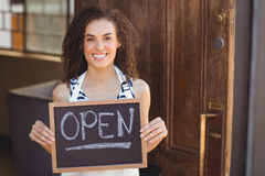Smiling waitress showing chalkboard with open sign Stock Image