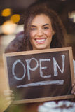Smiling waitress showing chalkboard with open sign Royalty Free Stock Photos