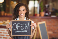 Smiling waitress showing chalkboard with open sign Stock Photo