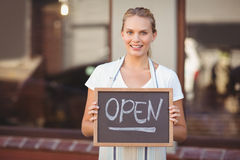 Smiling waitress showing chalkboard with open sign Stock Images
