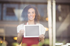 Smiling waitress showing a digital tablet Stock Image