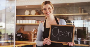 Smiling waitress showing slate with open sign