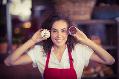 Smiling waitress showing two cupcakes Stock Images