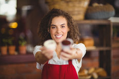 Smiling waitress showing two cupcakes Royalty Free Stock Photos