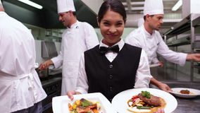 Smiling waitress showing two dishes to camera