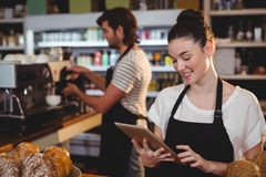 Smiling waitress standing at counter using digital tablet Royalty Free Stock Photos