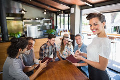 Smiling waitress standing by customers in restaurant. Portrait of smiling waitress standing by customers in restaurant Stock Photography