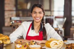 Smiling waitress standing over pastries. Portrait of a waitress standing over pastries at the coffee shop Royalty Free Stock Images