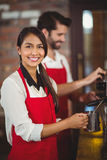 Smiling waitress steaming milk at the coffee machine Royalty Free Stock Photo