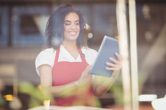 Smiling waitress using a digital tablet Royalty Free Stock Photography