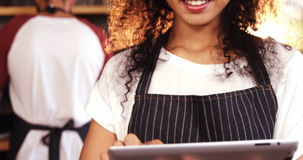 Smiling waitress using digital tablet at counter stock video