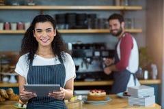 Smiling waitress using digital tablet at counter in café. Portrait of smiling waitress using digital tablet at counter in caf Royalty Free Stock Photos