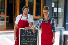 Smiling waitress and waiter standing with menu sign board outside café Stock Photos