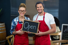 Smiling waitress and waiter standing with open sign board in café Royalty Free Stock Photography