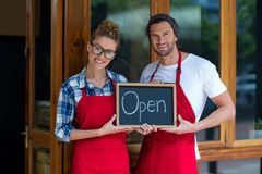 Smiling waitress and waiter standing with open sign board outside café Royalty Free Stock Image