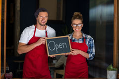 Smiling waitress and waiter standing with open sign board outside café Royalty Free Stock Photo