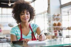 Smiling waitress writing on notepad Stock Images