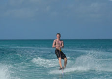 Smiling Wakeboarder on the Waters Off of Aruba. Smiling young guy riding a wakeboard in Aruba Royalty Free Stock Photography