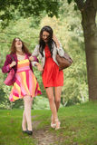 Smiling and walking. Two girls are having a lot of fun in the forest royalty free stock photo