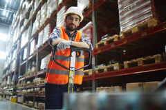 Smiling Warehouse Loader. Portrait of cheerful warehouse loader at work, pushing moving cart and looking at camera royalty free stock photo
