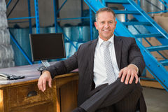 Smiling warehouse manage sitting with his legs crossed. In a large warehouse Royalty Free Stock Image