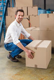 Smiling warehouse manager with box Stock Image