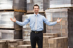 Smiling warehouse manager with hands out Stock Photography
