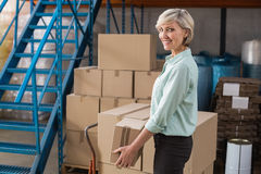 Smiling warehouse manager holding cardboard box. In a large warehouse Royalty Free Stock Image