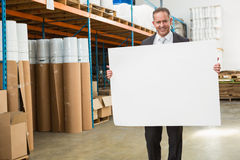 Smiling warehouse manager holding large white poster Stock Images