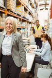 Smiling warehouse manager leaning on desk Stock Image