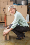 Smiling warehouse manager picking up cardboard box. In a large warehouse Royalty Free Stock Photo