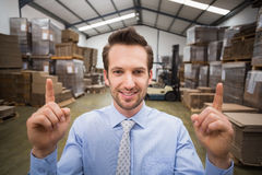 Smiling warehouse manager pointing up with finger Stock Images