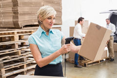 Smiling warehouse manager scanning package Stock Photos