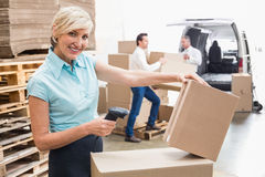 Smiling warehouse manager scanning package Stock Photography