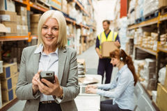 Smiling warehouse manager using handheld Stock Photo