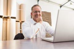 Smiling warehouse manager using laptop royalty free stock photo