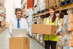 Smiling warehouse manager using laptop Stock Photography