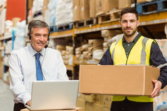 Smiling warehouse manager using laptop Stock Images