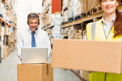 Smiling warehouse manager using laptop Royalty Free Stock Photos