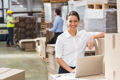 Smiling warehouse manager using laptop Royalty Free Stock Images