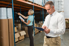 Smiling warehouse manager using tablet pc Stock Photography